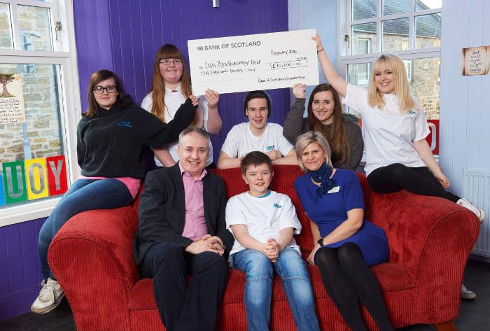 People sitting on sofa with an oversized check held overhead