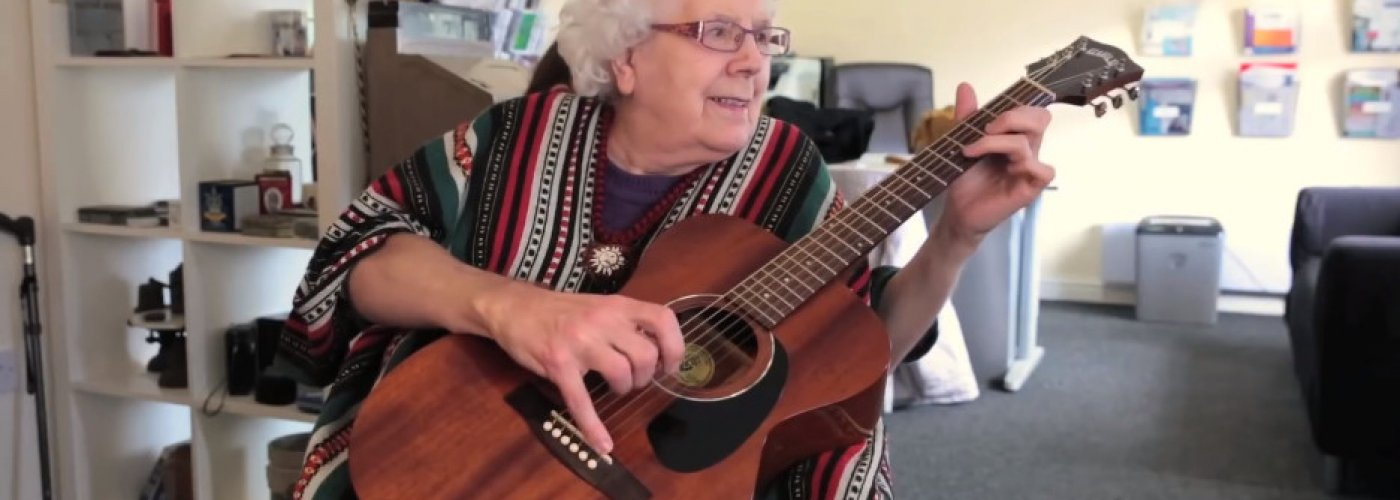 Grey haired woman playing a guitar